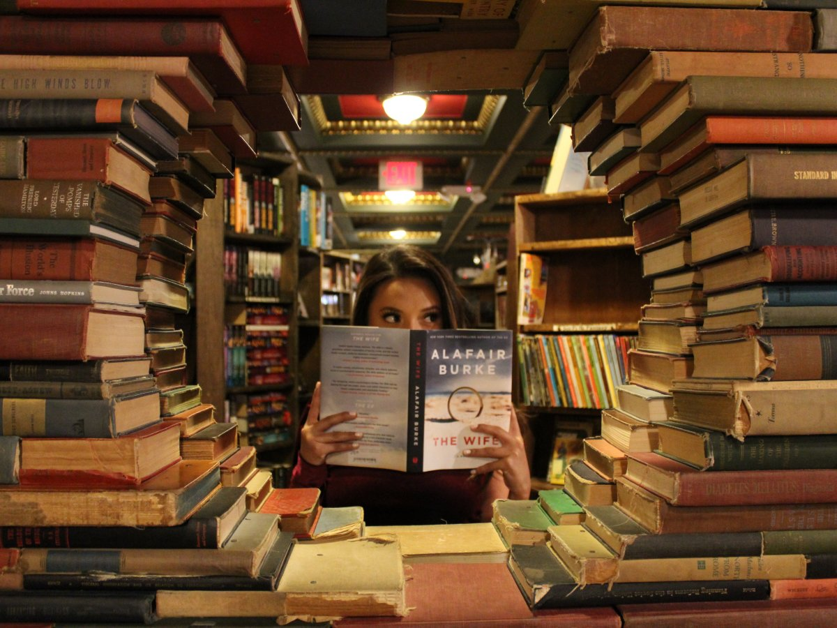 Girl reading book surrounded by books at library - Blueprint Career Development